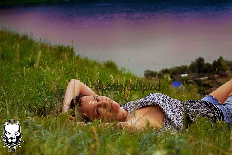 Woman lying on grassy field against sky during sunset