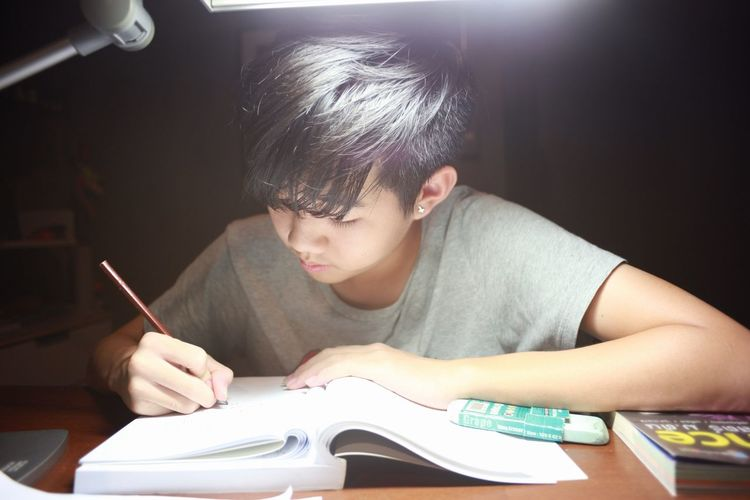 study hard Asian Boy Teenager Reading A Book Reading Study Time Study Hard Exam Child Learning Sitting Technology Concentration Arts Culture And Entertainment Headshot Males  Education Holding Pencil Homework Textbook Knowledge