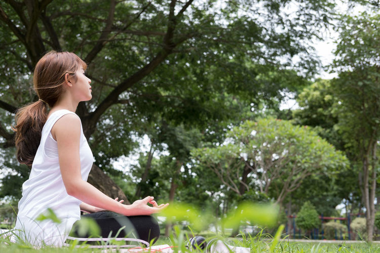 Side view of young woman doing yoga at park