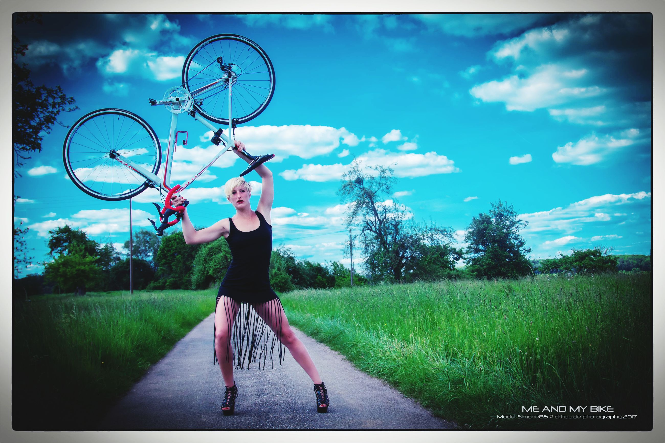 WOMAN WITH BICYCLE ON GRASS