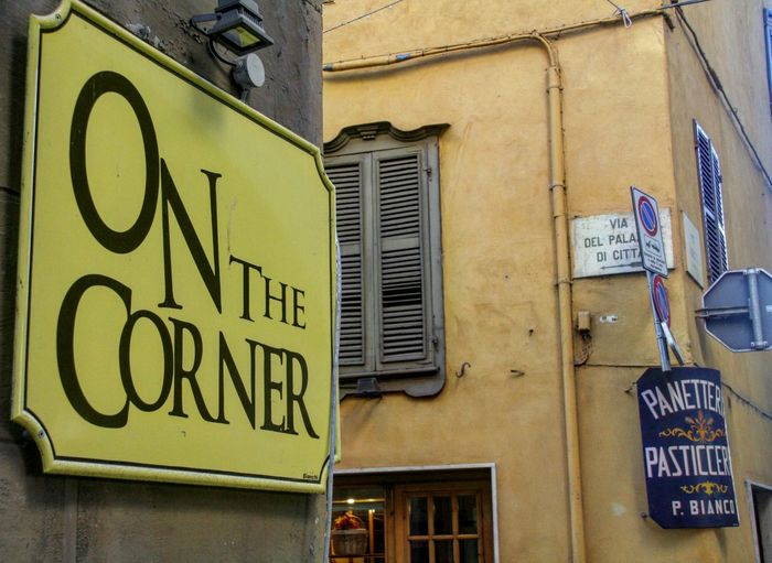 on the corner cafe Saluzzo Italy Building Exterior Architecture Outdoors Low Angle View Text Built Structure EyeEm Gallery Saluzzo  Popular Cultures Trending Photos Italy EyeEmBestPics Eyeem Market Uniqueness EyeEm Team Popular Photos Cafe Sign Shop Signs Italian Cafe Paint The Town Yellow