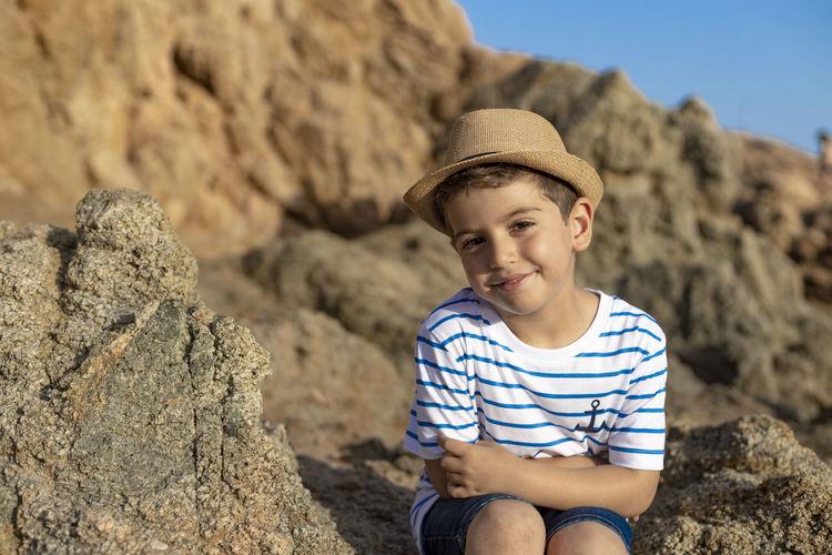 Portrait of cute boy wearing hat sitting on rock