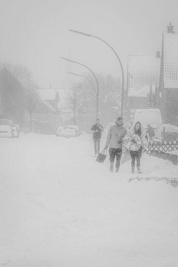 People walking on snow field against sky during winter