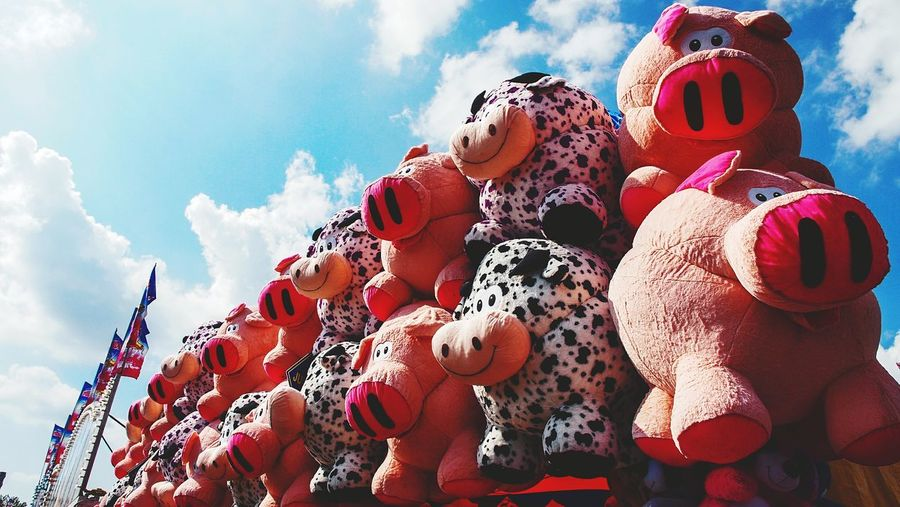 Low angle view of stuffed toys against sky at amusement park
