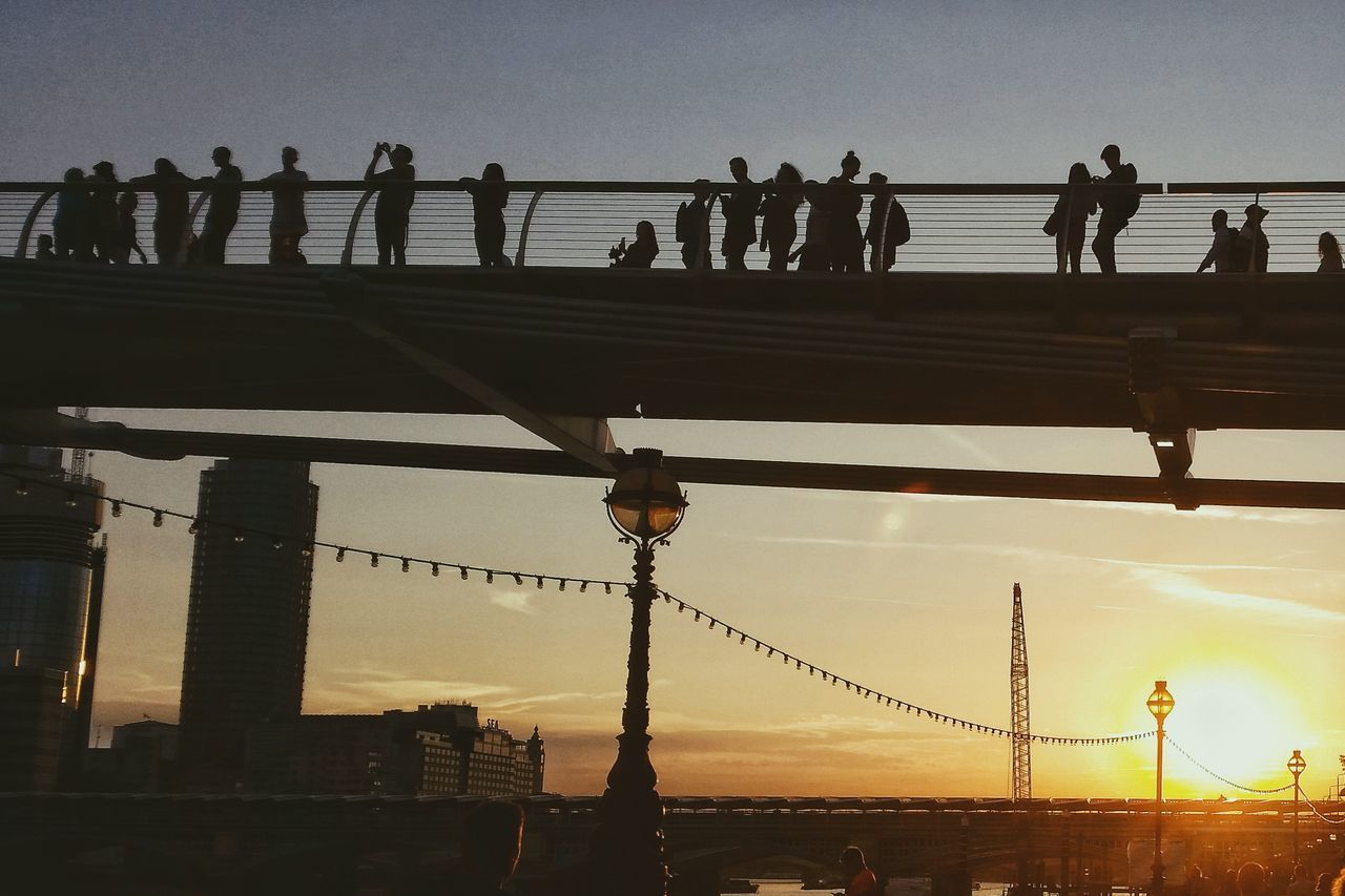 Silhouette People Standing On Bridge During Sunset