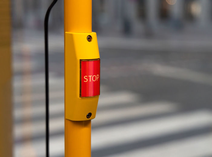 Close-up of yellow sign on pole in city