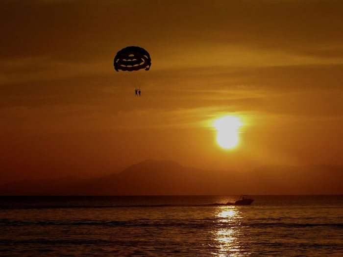 fly me to the sun.... EyeEm Gallery EyeEm Best Shots Eye4photography  Eyem Best Shots Hot Air Balloon Water Flying Sunset Mid-air Sun Business Finance And Industry Adventure Rippled Sky Silhouette Paragliding Parachute Calm Shore Idyllic Coast Parasailing Gliding
