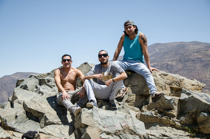 Full length of friends sitting on rock against clear sky