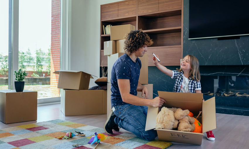 Little boy playing with his father while preparing the moving boxes Family Fun Happiness Happy Horizontal Man Moving Unpacking Writing Boxes Boy Cardboard Home Interior House Indoors  Kid Lifestyles Living Room New Home Packing Painting Placing Real People Relocating Two People