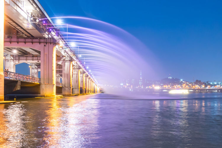 Moonlight rainbow fountain on banpo bridge over han river at dusk