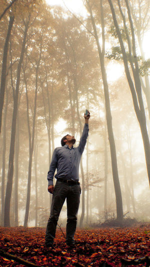 Full length of man standing with arms raised in forest during autumn