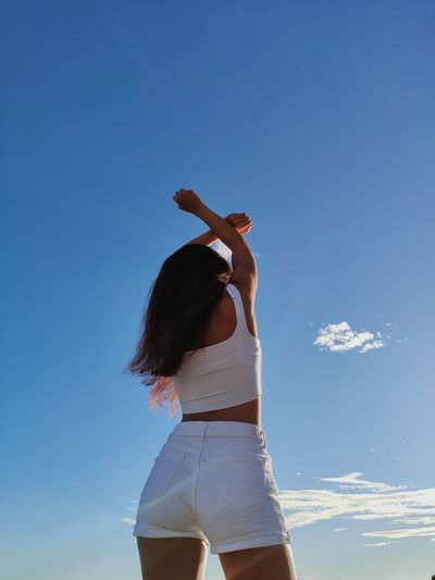 Rear view of woman standing against blue sky