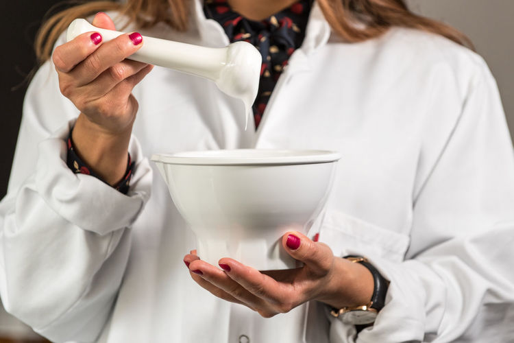 Close-up of pharmacist holding mortar and pestle
