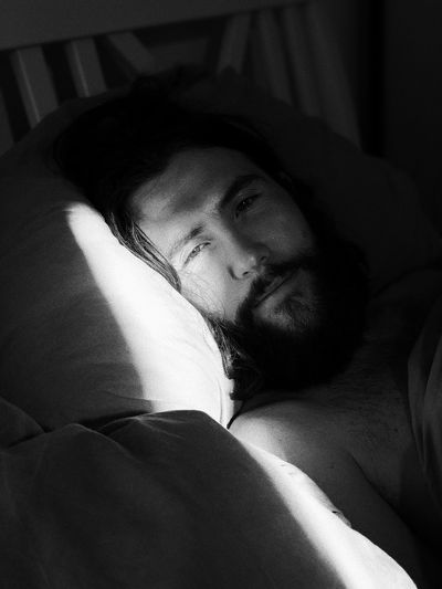 Portrait Of Man Lying On Bed At Home