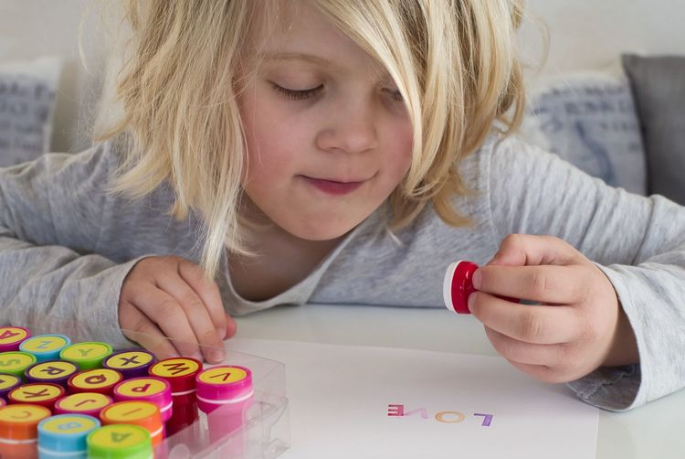 Peace, love and understanding. Documentary Reportage High Key Colorful Papercraft Paperwork Hobby School Girl Playing Paper Stockphoto Expressing Love Love Stamping Stamps Paper Craft Crafting Blond Hair Hair Child Childhood Leisure Activity One Person Multi Colored Art And Craft Creativity