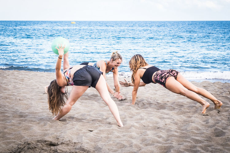 Females Exercising On Sand