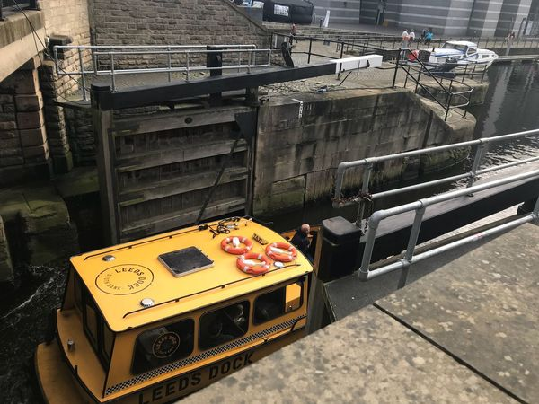 Water taxi travelling through the lock gates. Leeds Dock Yellow Boat Water Taxi High Angle View Transportation Mode Of Transport Industry Land Vehicle Day No People Outdoors