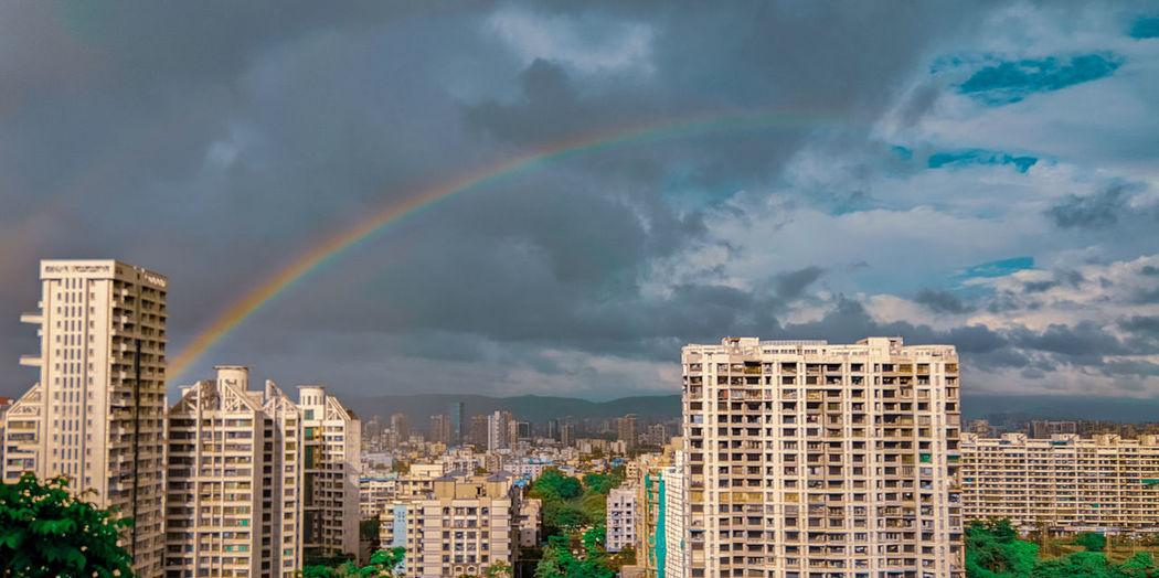 Rainbow over buildings in city against sky