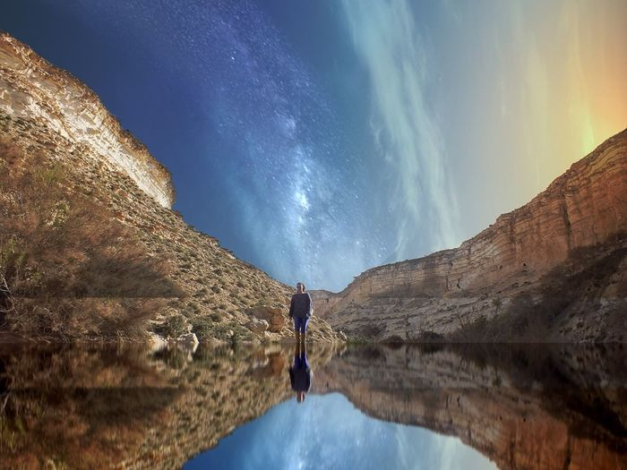 Reflection of woman and rock formation in lake against sky at night