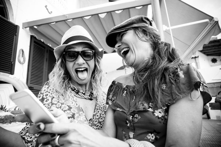 Black and white couple of young crazy women have fun together laughing a lot and doing expression taking a selfie picture with the phone - friendship and cheerful happy people concept Two People Happiness Young Women Real People Lifestyles Young Adult Leisure Activity Smiling Emotion Women Friendship Fashion Adult Togetherness Glasses Fun Front View People Technology Mouth Open Wireless Technology Crazy Moments Vacations Summer Hats Tongue Laugh Cheerful Selfie Mobile Phone Photography Happiness Holiday Travel Tourist
