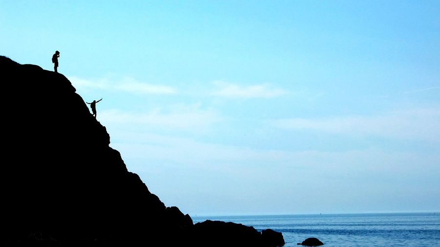 Low angle view of silhouette men on cliff by sea against blue sky