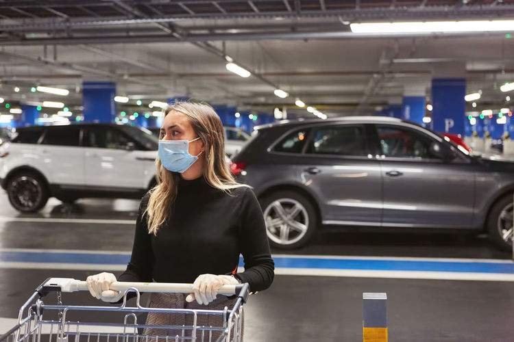 Young woman wearing mask at parking lot