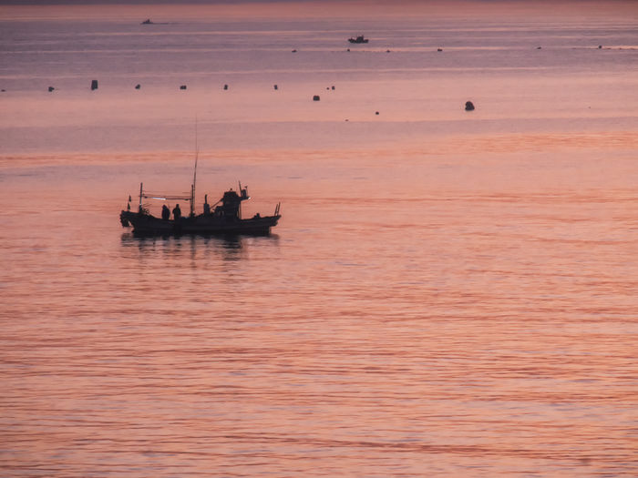 Fishing boat sailing in sea during sunset