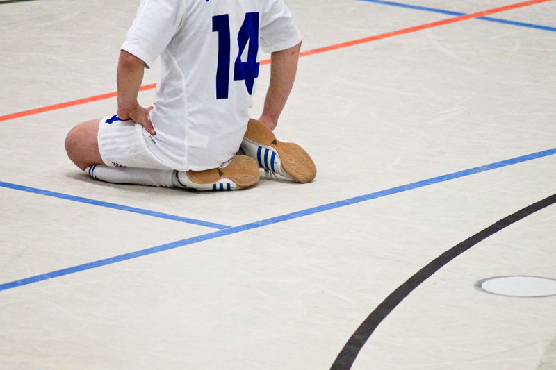 Low Section Of Soccer Player Kneeling At Court