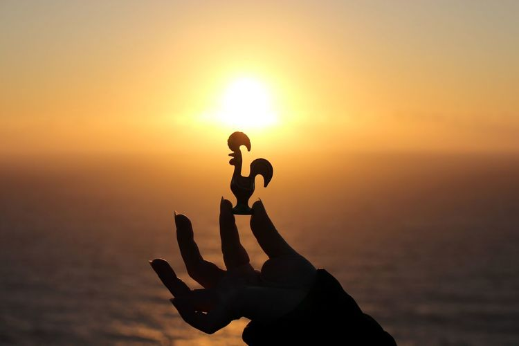 Cropped image of person holding silhouette rooster figurine by sea against sky during sunset