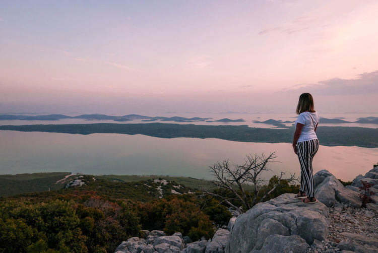 Rear view of woman standing on cliff with amazing view, seascape, islands.
