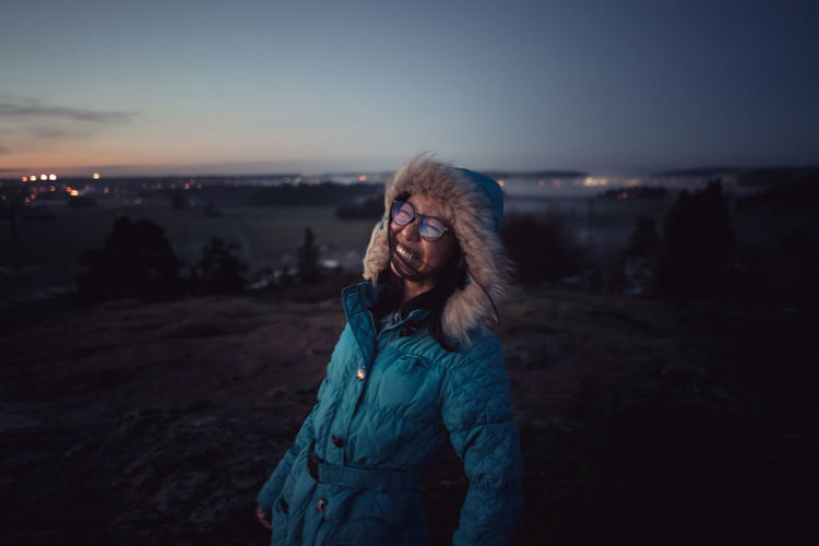 Portrait of Asian girl wearing blue winter jacket with hood on laughing and smiling at camera during sunset Asian Woman Happy Adult Asian Girl Black Hair Chinese Eyeglasses  Nature Night One Person Only Women Outdoors People Real People Sky Standing Sunset Warm Clothing Young Adult Young Women EyeEm Ready