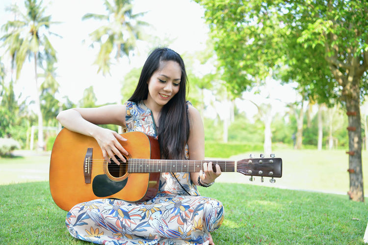 Young woman playing guitar while sitting at park