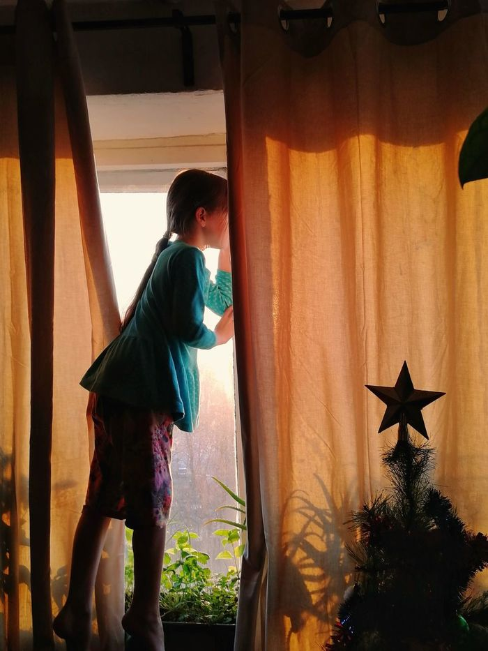 Side view of girl standing by window at home