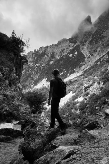 Rear view of man walking on rocks against mountains