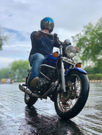 Rainy days One Person Transportation Real People Lifestyles Ride Mode Of Transportation Riding Full Length Motorcycle Road Helmet Day Leisure Activity Men Nature Sky Outdoors City
