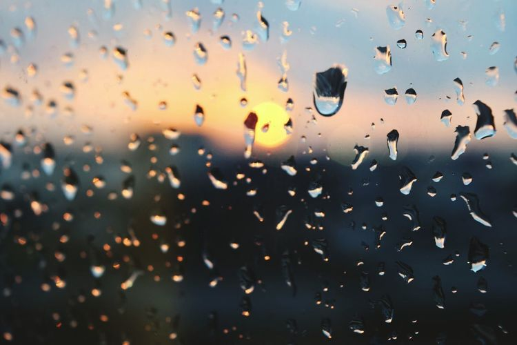 Sky seen through wet glass window during sunset