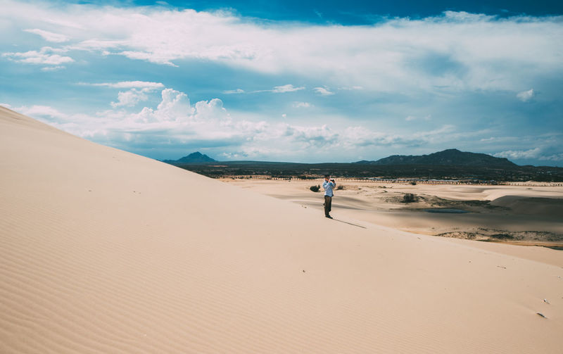Man standing on sand dune at desert against cloudy sky