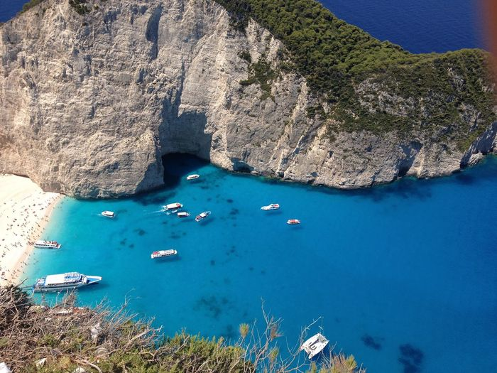 High Angle View Of Boats Moored By Rock Formation In Blue Sea