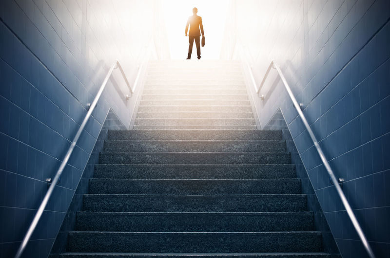 Rear view of a businessman climbing stairs, Concept into success. Success Business Concept Businessman Successful Stairs Career Achievement Climbing Top Up Growth Steps Ladder Way Step Work Job City Climb Walking Leadership Finance person Subway Railing Station Steel Staircase Light Metal Urban Background Stainless Architecture Stair Marble Modern Escalator Building Wall Construction Interior Floor Hall Stairway Creative Leader