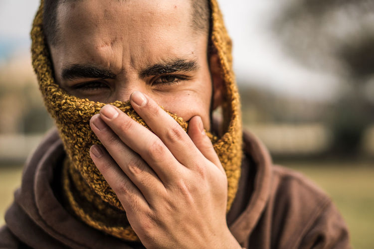 Close-up portrait of man covering face standing outdoors