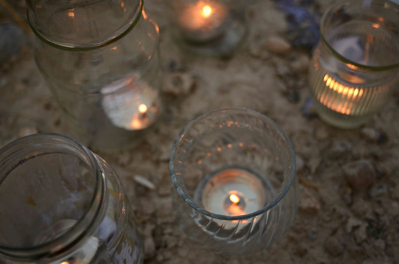 High angle view of illuminated tea light candles in glasses