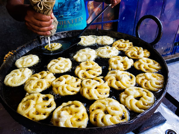 Jalebi an indian sweet dish being fried in sugar syrup in a large container Jalebi Business Close-up Food Food And Drink Freshness Fried Sweets Healthy Eating High Angle View Household Equipment Human Body Part Human Hand Indoors  Jilipi Kitchen Utensil Midsection One Person Preparation  Preparing Food Ready-to-eat Real People Snack Sugar Syrup Sweet Dish  Wellbeing
