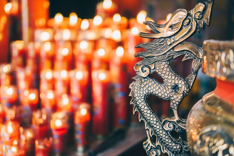 Close-up of illuminated candles and metallic sculpture
