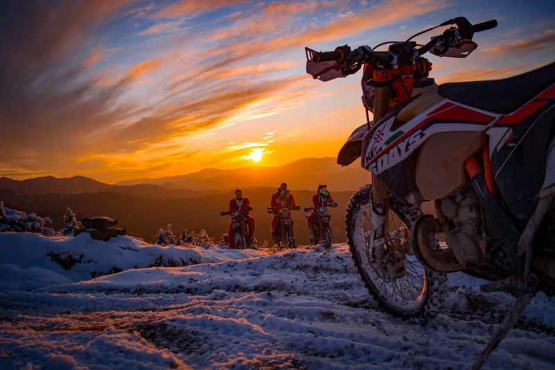 People riding bicycles on snow covered land during sunset