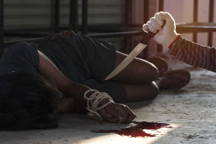 Burglar aiming knife on unconscious tied woman lying on floor