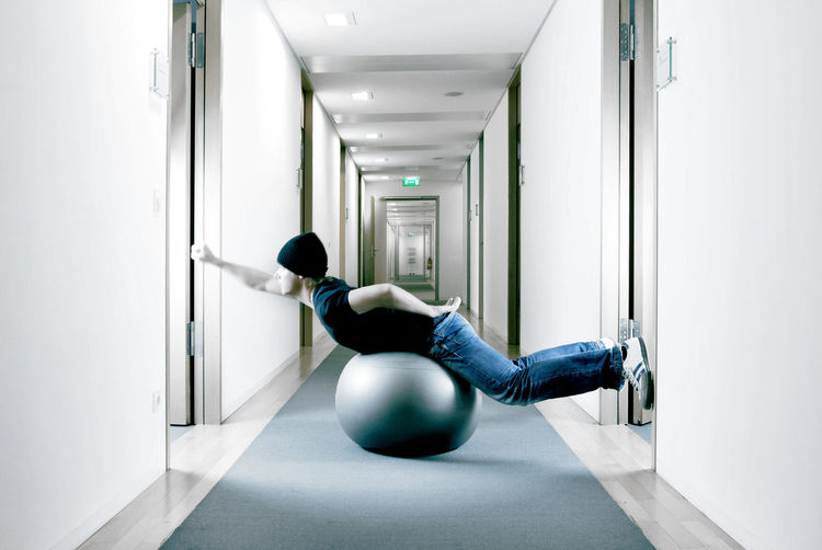Side view full length of man exercising on fitness ball in corridor