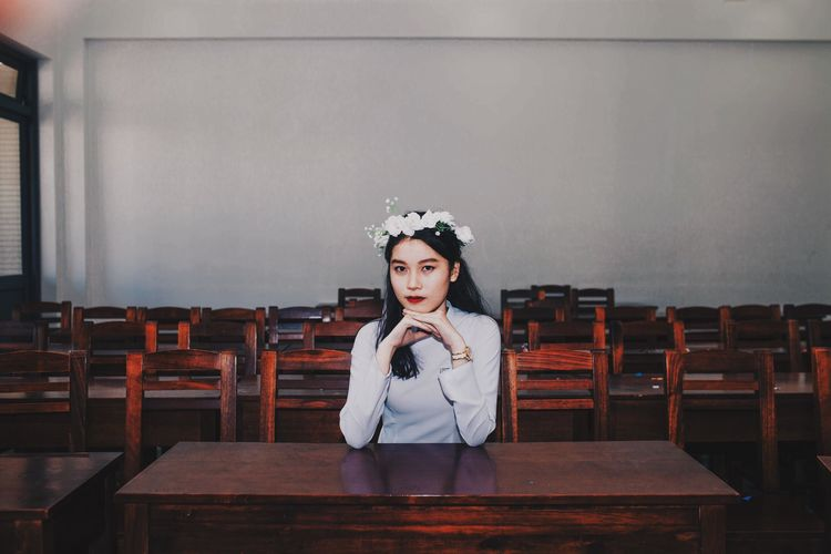 Portrait Of Young Woman Sitting At Table Against Wall