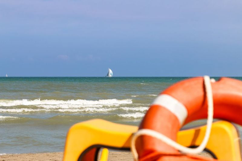 Vew from shore to sailing boats far to the sea, Italy, Riccione Emiliaromagna Rimini Seascape Italy. Riccione Riccione Italy Sailboat Beach Orange Color Yellow Lifebuoy Sea Water Horizon Over Water Beach Nature Beauty In Nature Day Outdoors Wave No People Sky