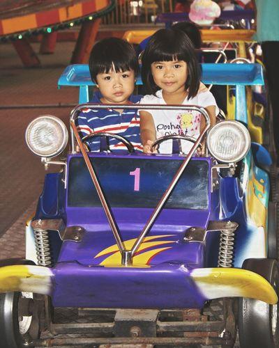 Portrait Of Siblings Sitting In Bumper Car At Amusement Park
