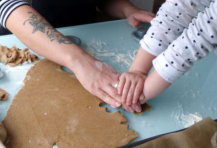 Cropped hands of mother and daughter preparing cookie in kitchen at home